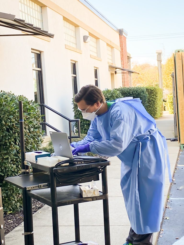 Employee from PCP PrimeCARE working outside on a laptop